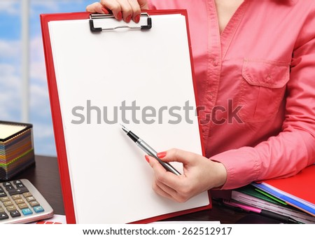 woman showing blank clipboard sitting in office - stock photo