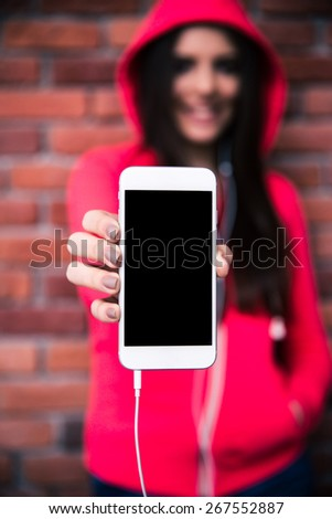 Woman showing blank smartphone display over brick wall. Focus on smartphone - stock photo