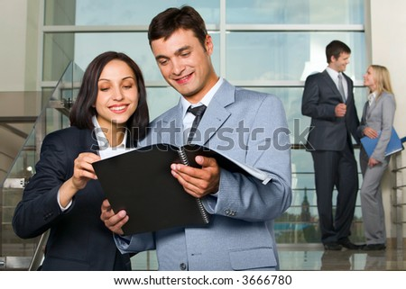 Woman showing documents to her colleague on stairs in the building with glassy walls and couple of talking businesspeople on the background - stock photo
