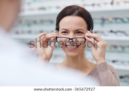 woman showing glasses to optician at optics store - stock photo