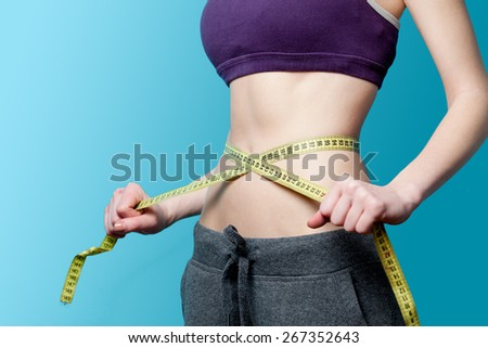 Woman showing her abs with metric after weight loss on blue background - stock photo