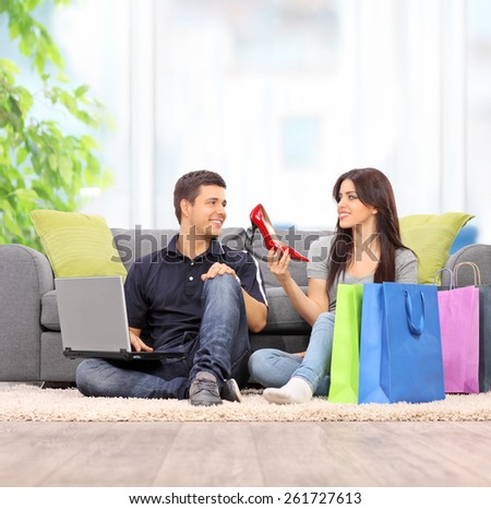 Woman showing her new shoes to boyfriend at home shot with tilt and shift lens - stock photo