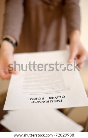 Woman showing insurance claim form to you, shallow DOF. - stock photo