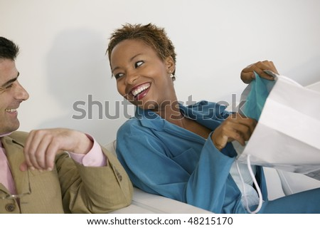 Woman Showing Man Purchases in Shopping Bag - stock photo
