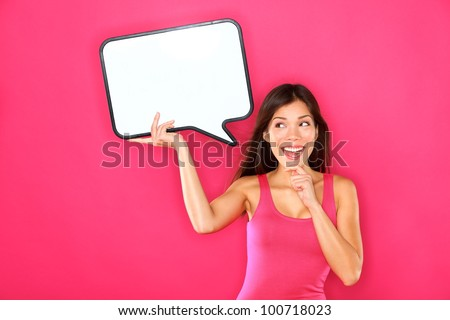 Woman showing sign speech bubble banner looking happy excited on pink background. Beautiful young multiracial Caucasian / Asian Chinese joyful model on pink background having idea. - stock photo