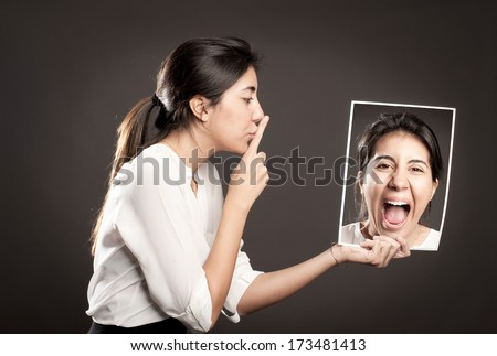 woman showing silence gesture and holding a portrait of herself - stock photo