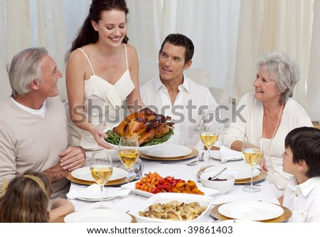 Woman showing turkey to her family for Christmas dinner at home - stock photo