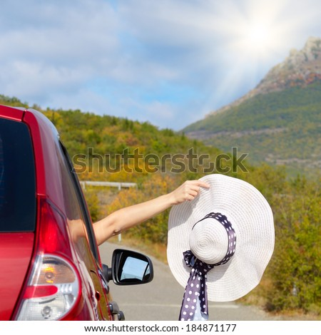 Woman shows sun hat from car window - Travel vacations concept - stock photo