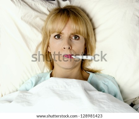 Woman sick in bed or hospital with thermometer in mouth - stock photo