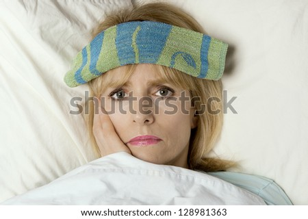 Woman sick in bed or hospital with washcloth on face - stock photo