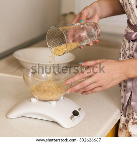Woman sifts rice in a bowl on kitchen scale - stock photo