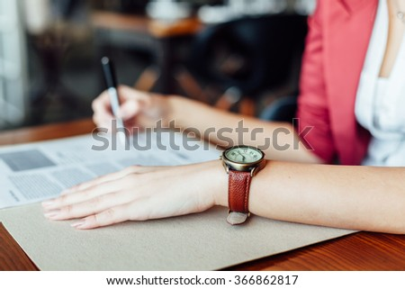 Woman signing contract with leather wristwatch in closeup - stock photo