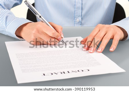 Woman signs contract at desk. Female signing contract at desk. Employer at the working desk. Recruiter at her workplace. - stock photo