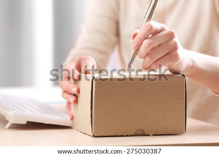 Woman signs parcel in post office - stock photo