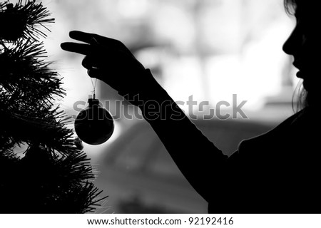 Woman silhouette dresses up Christmas tree (black white) - stock photo