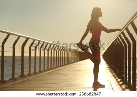 Woman silhouette exercising stretching on a bridge after running at sunset - stock photo