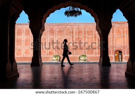 Woman silhouette with guidebook walking in the City Palace museum, Jaipur, Rajasthan, India - stock photo