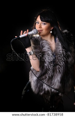Woman singer in fur coat on black background - stock photo