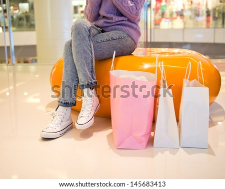 Woman sit at bench with bags in shopping mall - stock photo