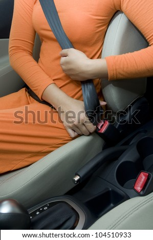 Woman sit on car seat and fasten safety belt - stock photo