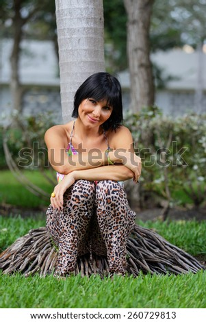 Woman siting by a tree and smiling - stock photo