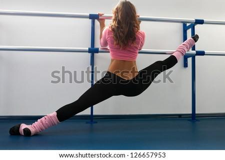 Woman siting on straddle split on bar in dance studio - stock photo
