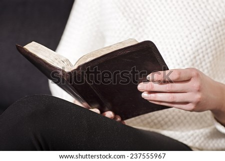 Woman sits and read the bible - stock photo