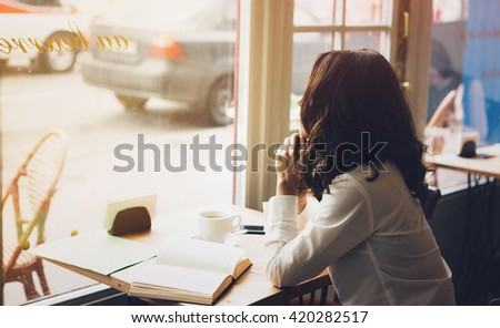 Woman sits in a cafe with a cup of coffee, tea. Read a book and dream. Look  out the window. Wait for somebody. - stock photo