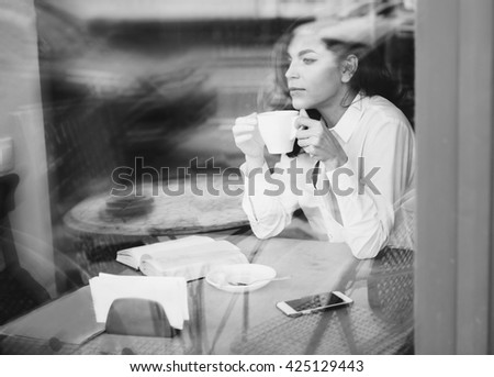 Woman sits in a cafe with a cup of coffee, tea. Read a book and dream. Look  out the window. Wait for somebody - stock photo