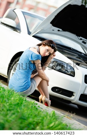 Woman sits on the grass near her broken car with the opened hood waiting for assistance - stock photo