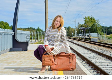 Woman sitting and holding a brown bag and vintage suitcase at train station - stock photo