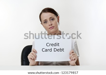 woman sitting at a desk worried about credit card debt problems - stock photo