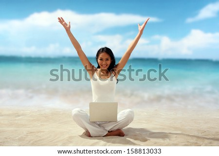 Woman sitting at beach with laptop on her legs - stock photo