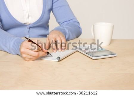 woman sitting at desk with , calculator, checkbook, pen and coffee cup - stock photo