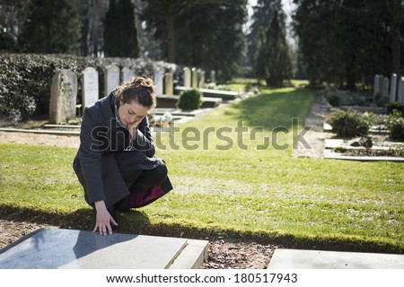Woman sitting at grave - stock photo