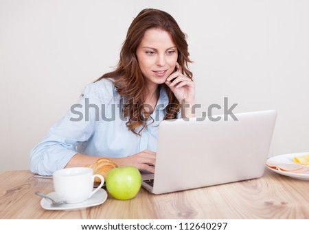 Woman sitting at her desk working on her laptop - stock photo