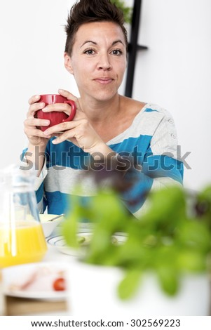 Woman sitting at the breakfast table holding a coffee cup with both her hands. - stock photo