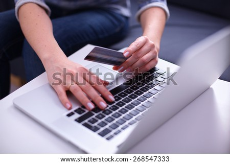 Woman sitting at the desk, shopping with laptop and credit card - stock photo