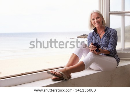 Woman Sitting At Window And Looking At Beautiful Beach View - stock photo