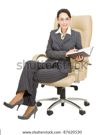 woman sitting in a chair with a notebook - stock photo