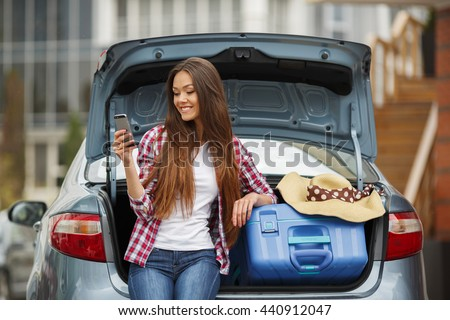 Woman sitting in back of car smiling. Getting ready to go. Young laughing woman sitting in the open trunk of a car. Summer road trip. Young woman sitting in the car trunk with suitcases - stock photo
