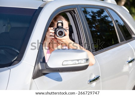 Woman sitting in car and photographing with camera at sunny day - stock photo