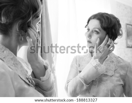 Woman sitting in front of a big mirror  	 	 	 	 	 	 	 	 	 	 	 A young girl sitting in front of a big mirror and looking away of her reflection, mirror stage concept shot.  - stock photo
