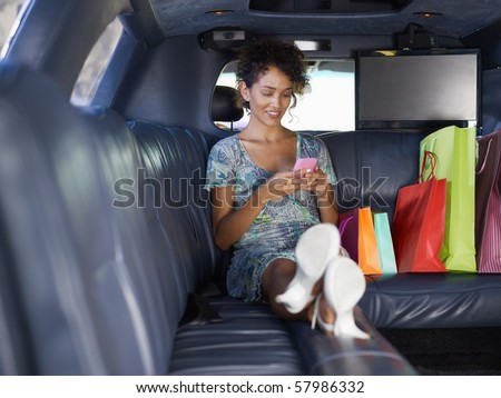 woman sitting in limousine with shopping bags and typing on mobile phone. Horizontal shape, full length, copy space - stock photo