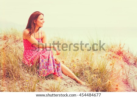 Woman sitting in sand at beach - stock photo
