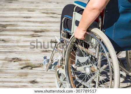 Woman sitting in self propelled wheelchair - stock photo
