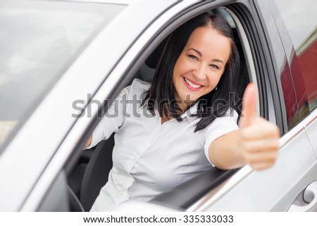 Woman sitting in the car and showing thumbs up  - stock photo