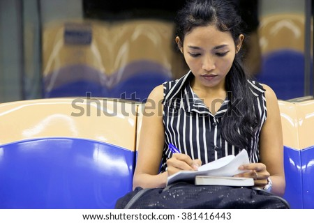 woman sitting in the subway car and writes notes. Passenger in the subway reading the notes. Passengers woman sitting in the wagon. Commuters woman studying his notes when she ride in the train. - stock photo