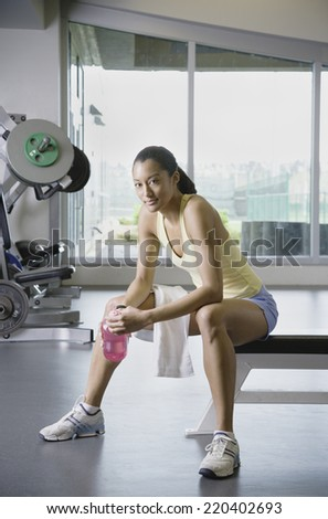 Woman sitting in weight bench at gym - stock photo