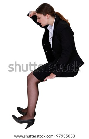 Woman sitting looking down - stock photo